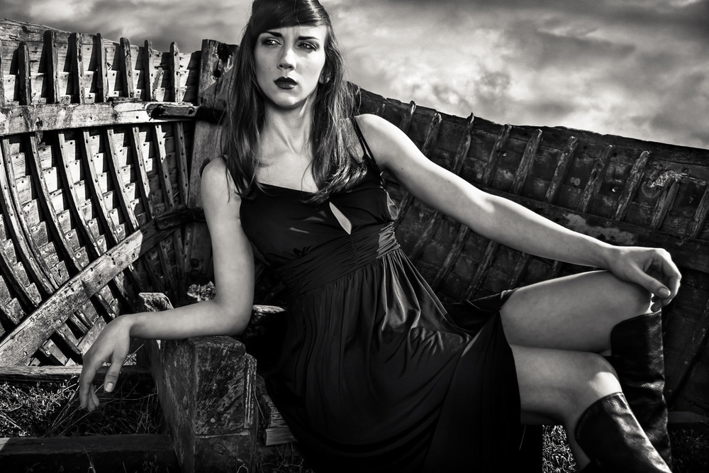 Female model wearing a black dress sitting in a Norfolk boat wreck