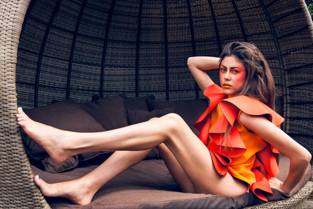Female model wearing orange Avant Garde swimwear and makeup