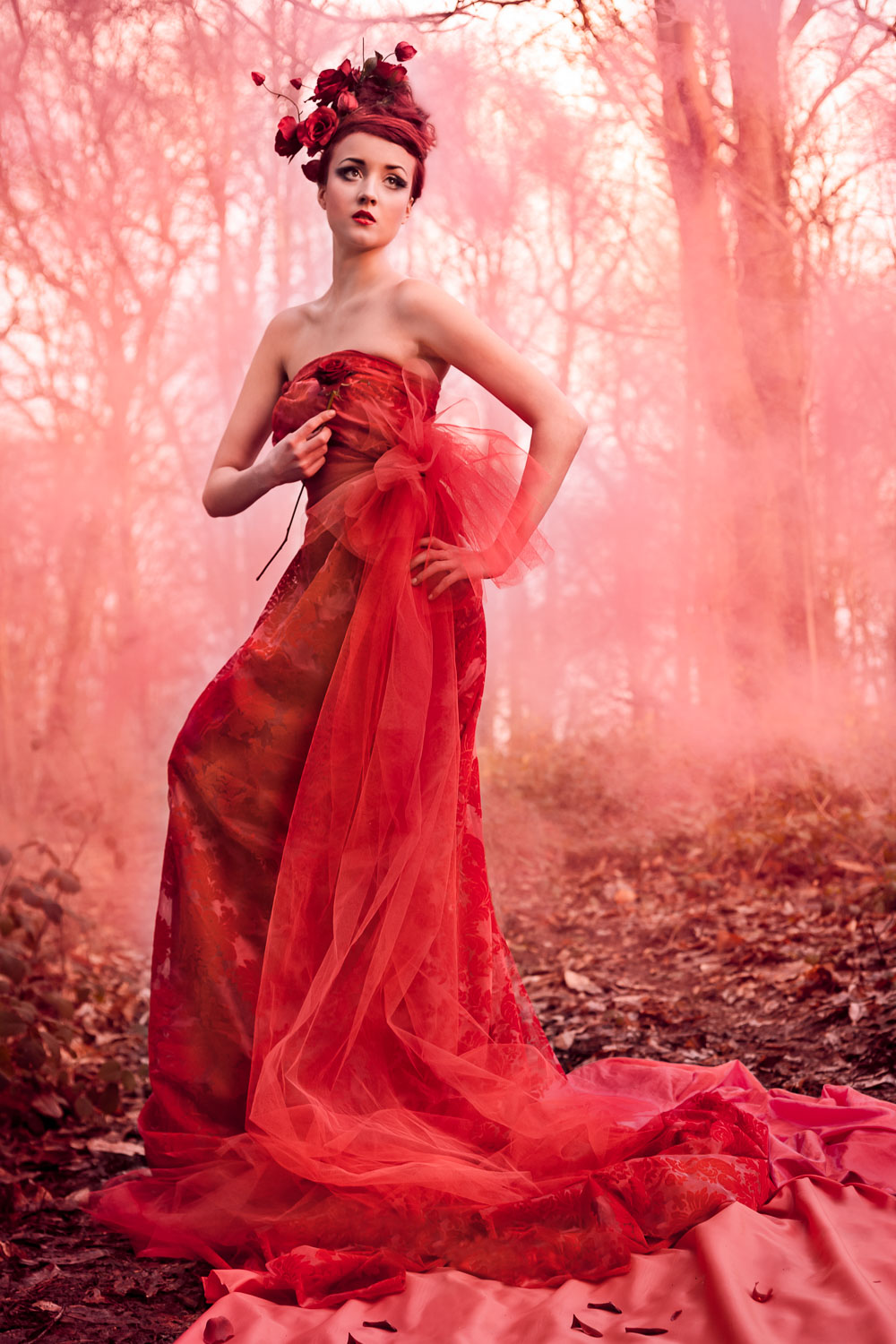Female model dressed as a red rose wearing a red dress and rose flower headpiece in an enchanted forest with red smoke