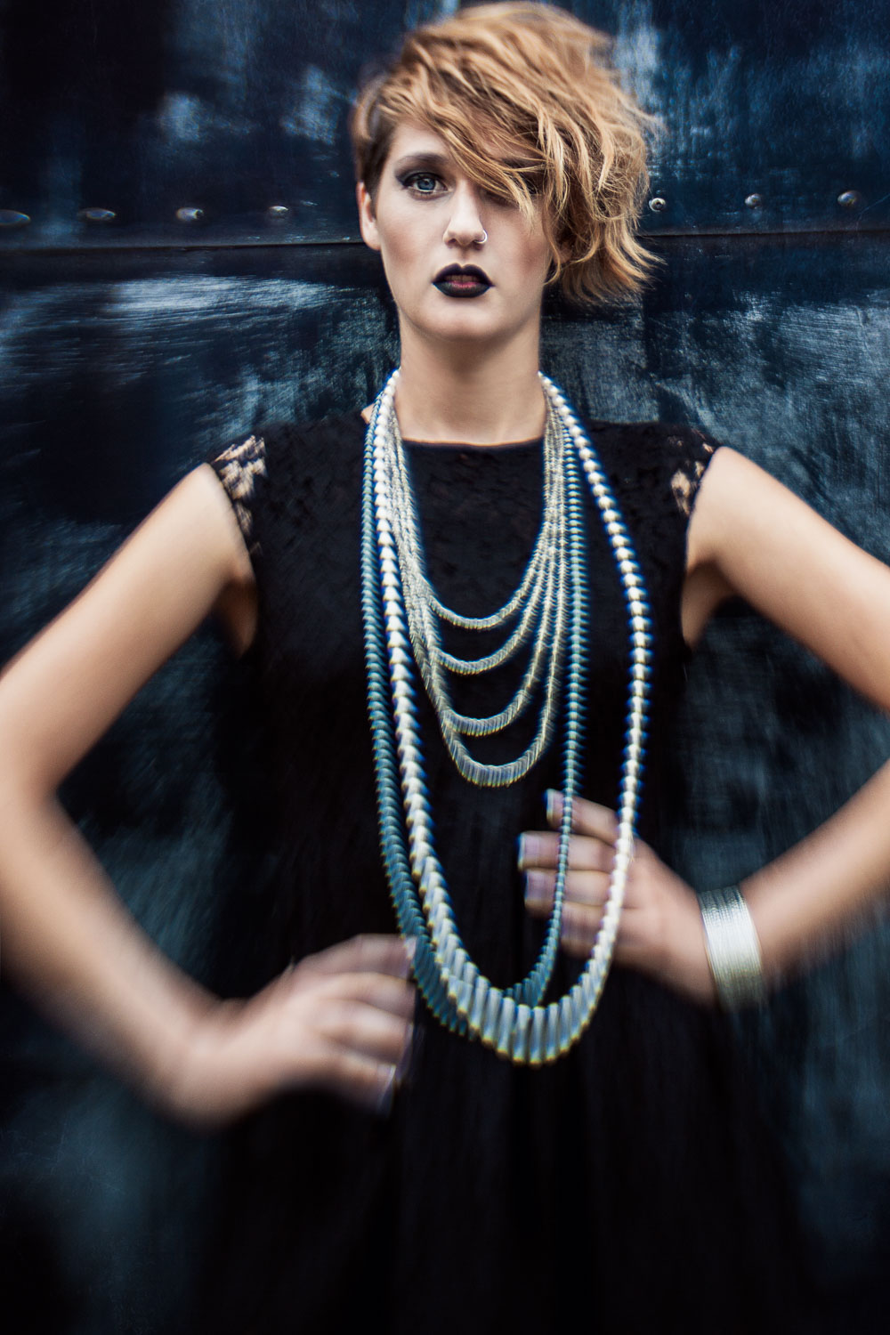 Female model wearing little black dress and beaded necklaces