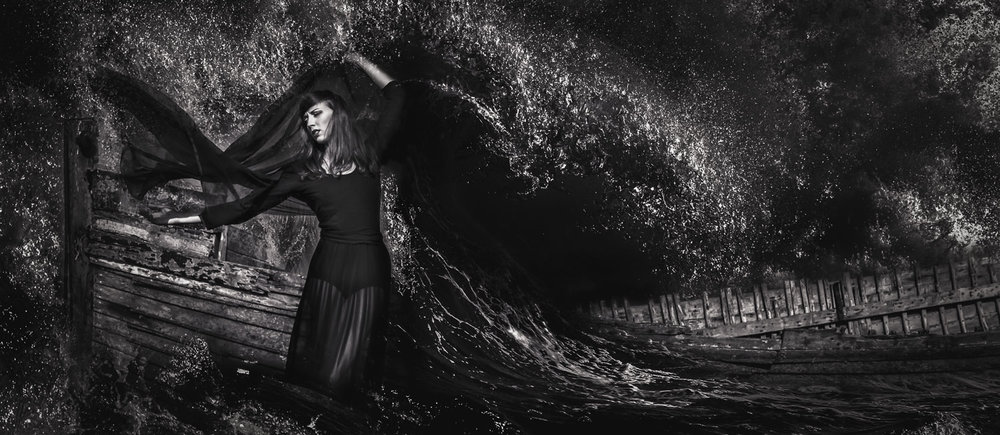Female model wearing black dress at a Norfolk boat wreck with crashing waves