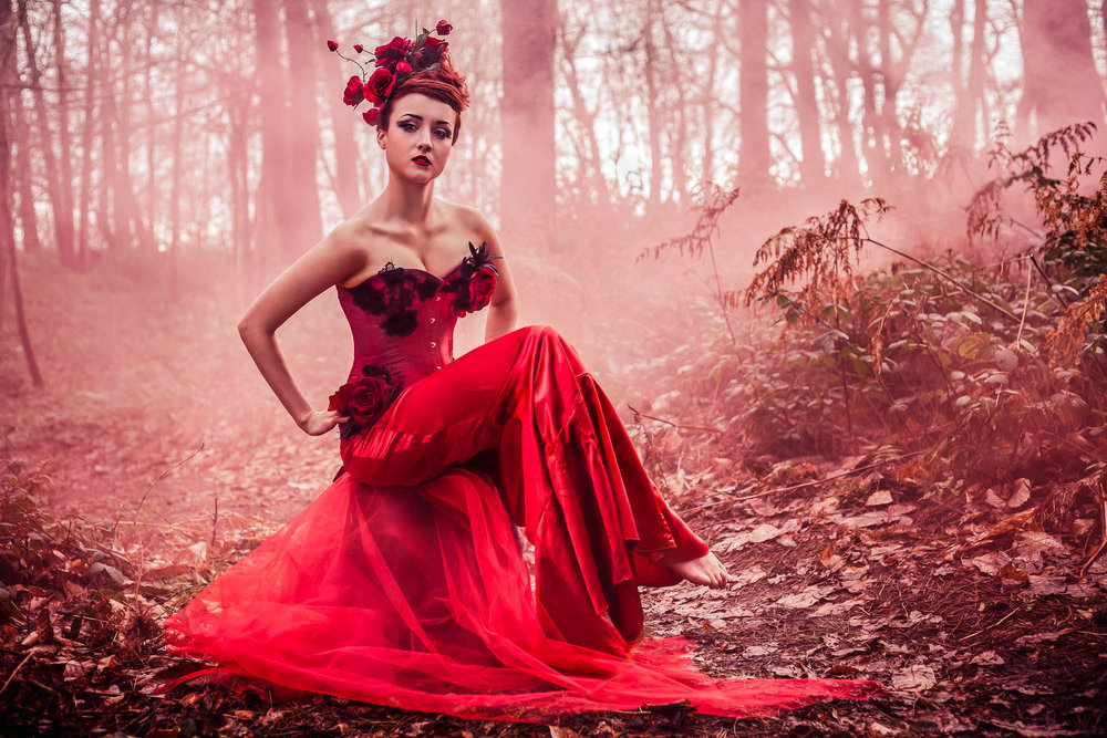 Female model in the woods wearing a red corset couture dress surrounded by red smoke captured by conceptual photographer Adrian Farr