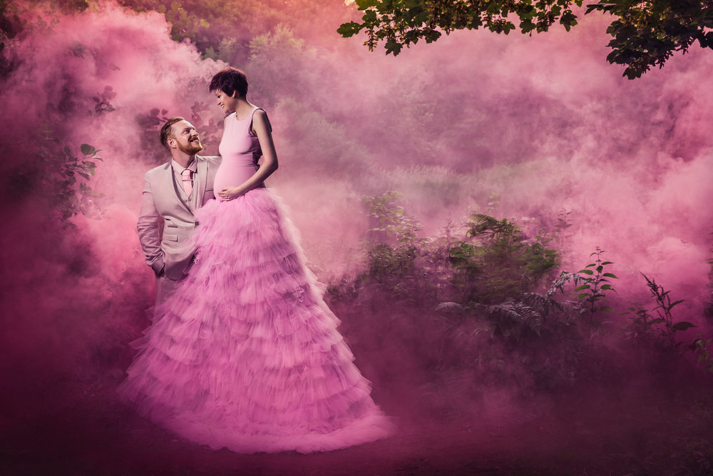 Expecting Mum wearing a long pink couture maternity gown holding her baby bump smiling at her partner Adrian Farr surrounded by clouds of pink smoke in the woods