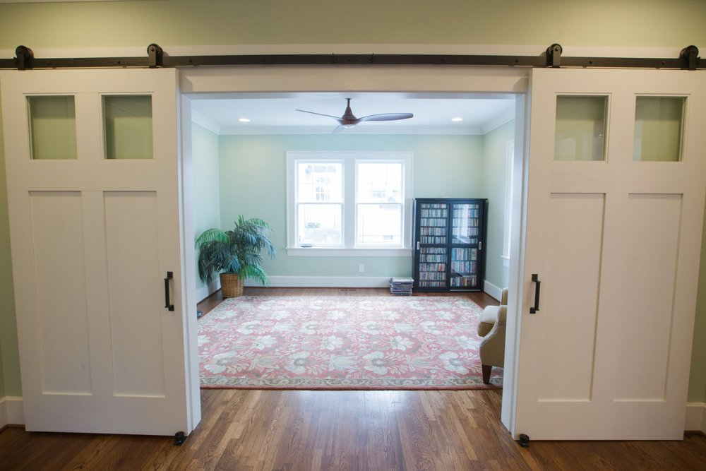 Barn doors with the perfect craftsman styling as well as windows allow for privacy, light, and integration into the rest of the design.