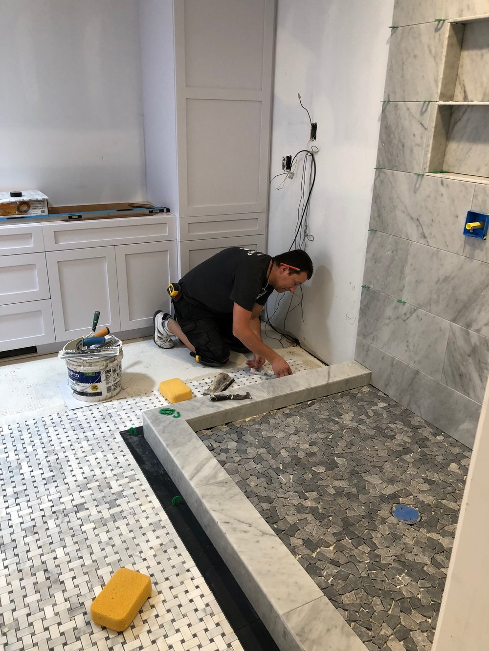 Cristian, the tile master, finishes up the tile in the Van Nort bathroom renovation.
