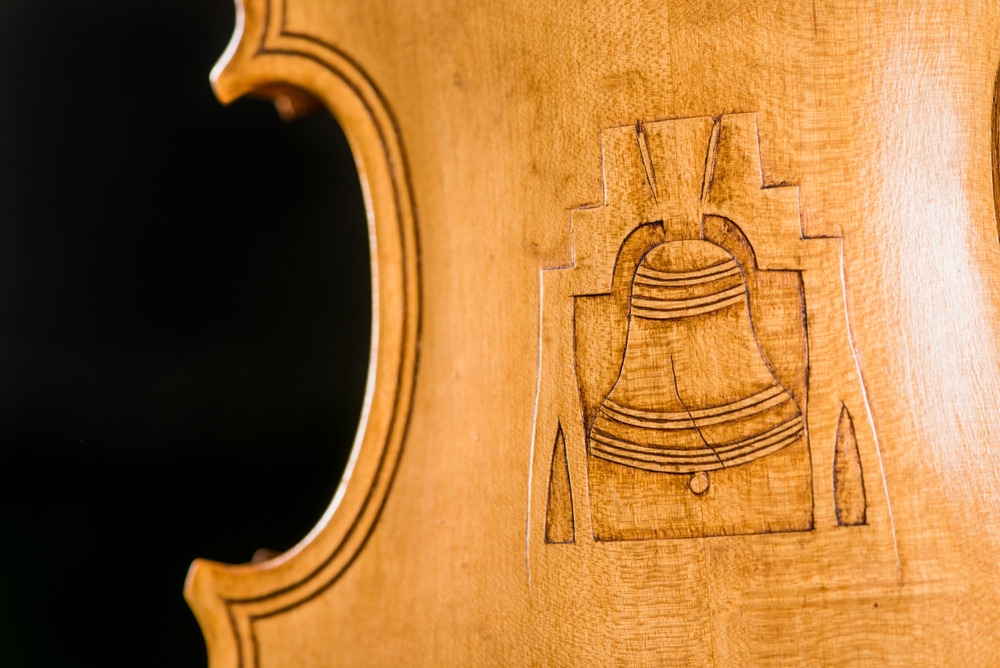 A fiddle carved by Denton Boze with a pocket knife and adorned with an image of the Liberty Bell on the back.