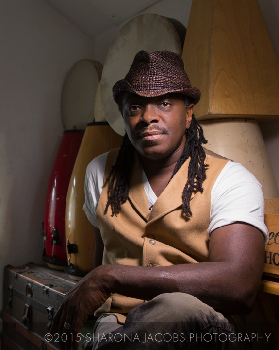 Portrait of Regie Gibson in front of his drum collection