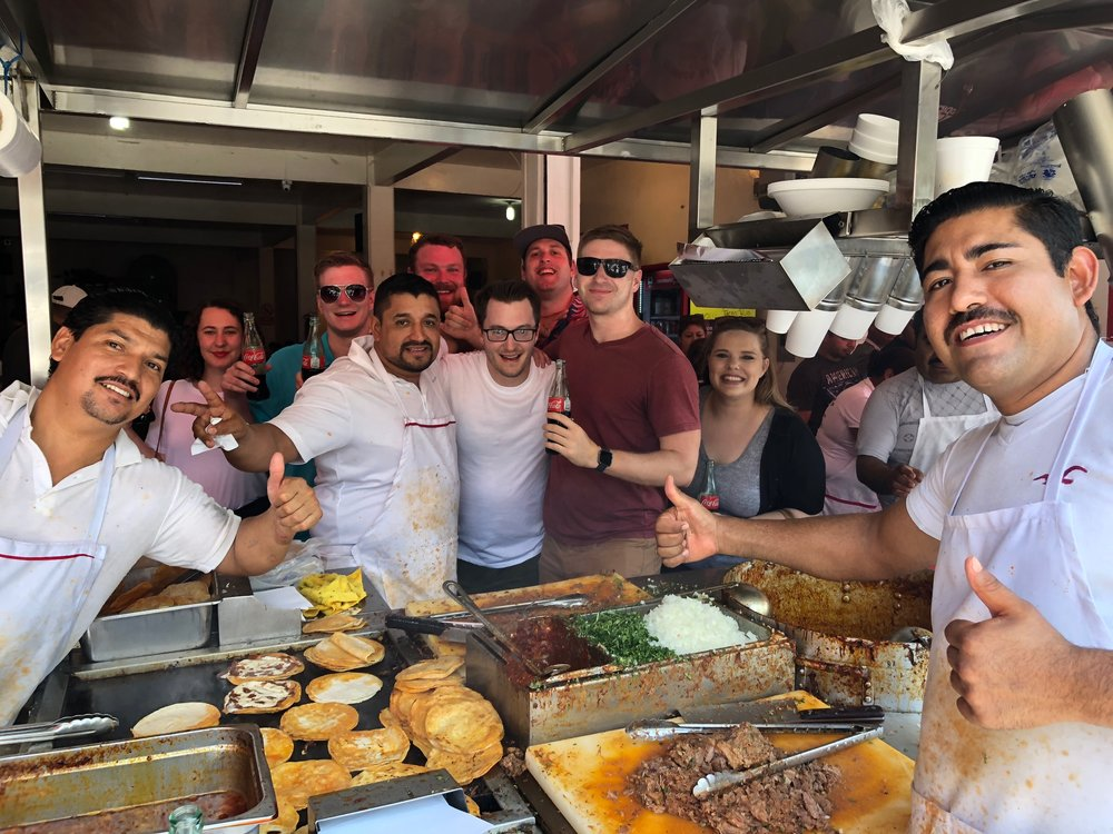 "James and his group taking a photo with some of Tijuana's most famous ""taqueros."" James proclaimed these beef tacos de birria ""the best tacos I've ever eaten!"" (we hear that a lot)"
