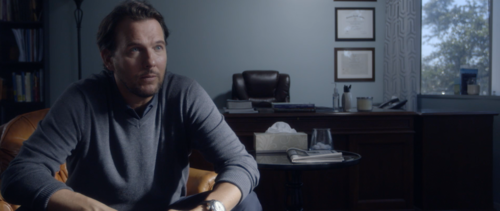 Jonah, played by Jay Huguley, sitting in his office.