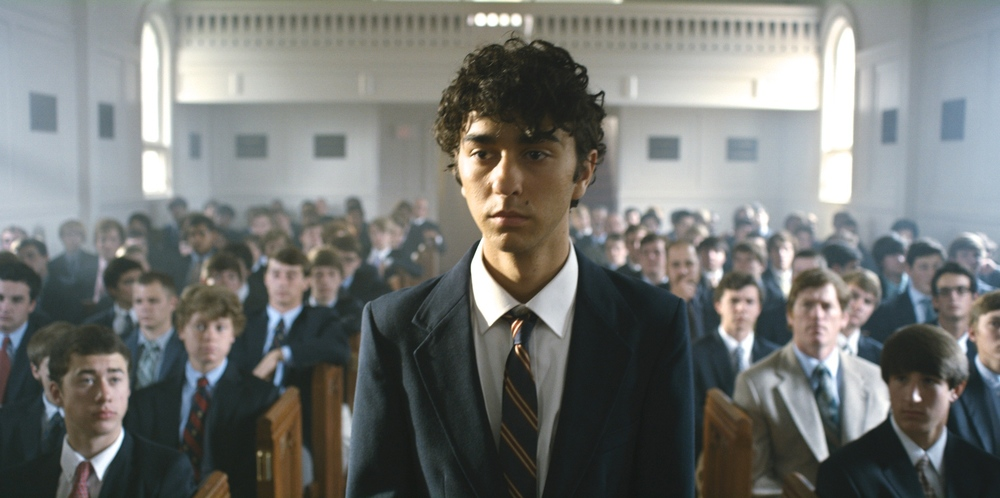 Jamie, played by Alex Wolff, walks down the auditorium aisle at his boarding school.