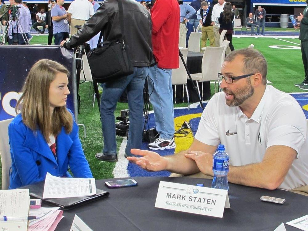Elizabeth Cotter speaks with Michigan State offensive line coach Mark Staten on Dec. 29 at AT&T Stadium in Arlington, Texas
