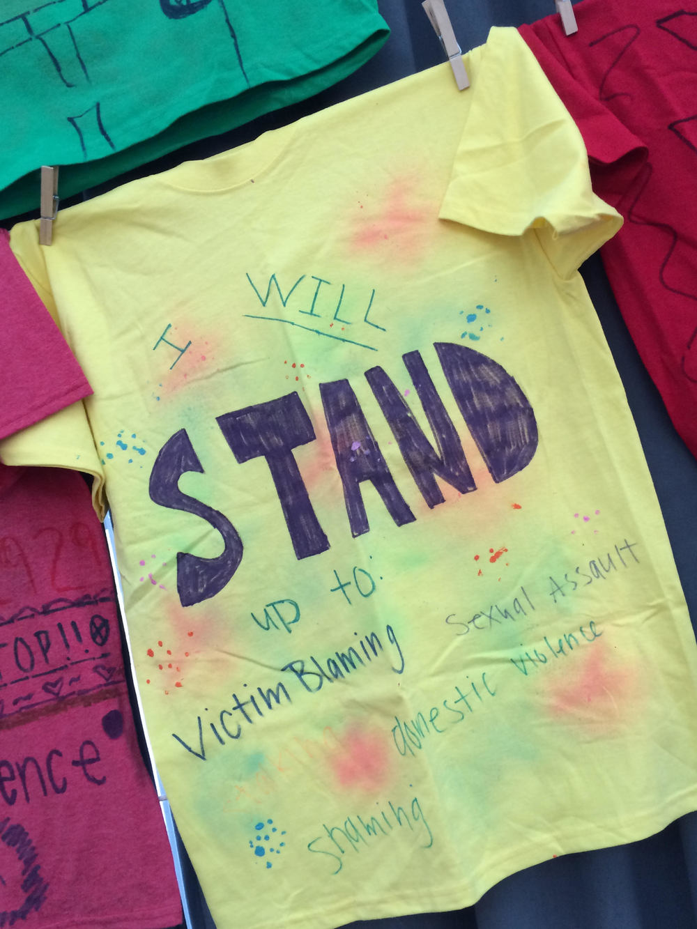 "Yellow T-shirt that says ""I will Stand up to: victim blaming, sexual assault, domestic violence, and shaming."""