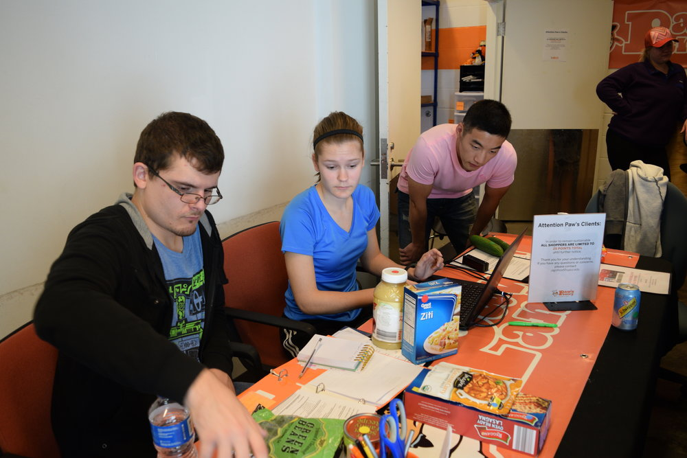 Volunteers Christopher Enochs, Laura Lentz, and Andy Bai ring up a patron at Paw's Pantry.