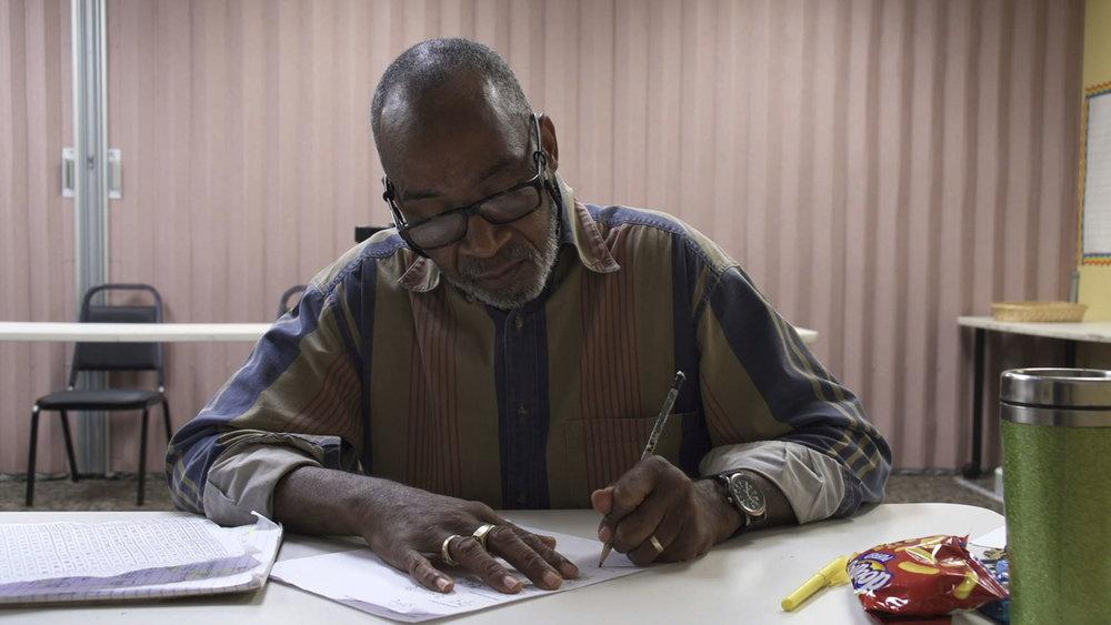 "Greg studies in a still from ""Night School."" (Photo from nightschoolfilm.com)"