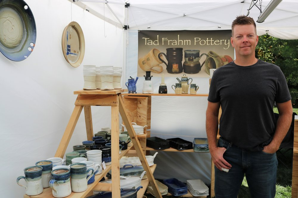 Ted Frahm poses with his pottery, featuring work from mugs to casserole dishes.