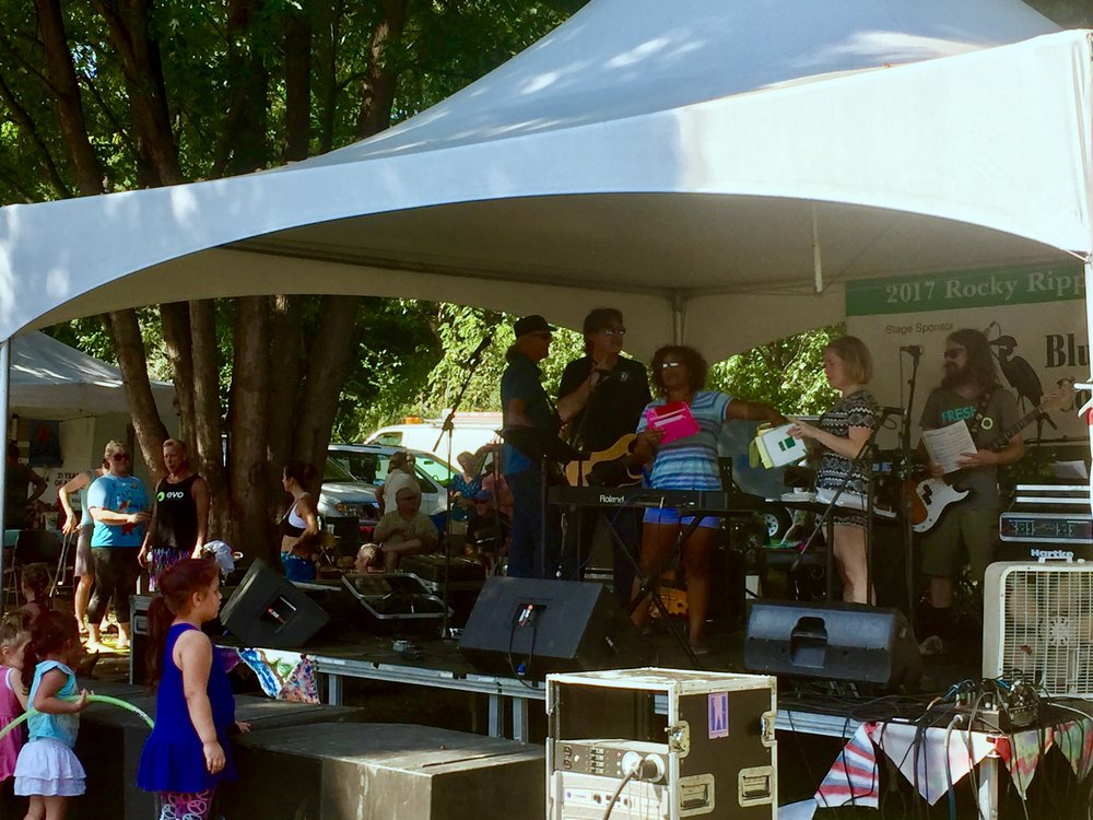 Festival MC Tracy Fouts, on stage with Tim Brickley and The Bleeding Hearts as she reads off the winners of the raffle.