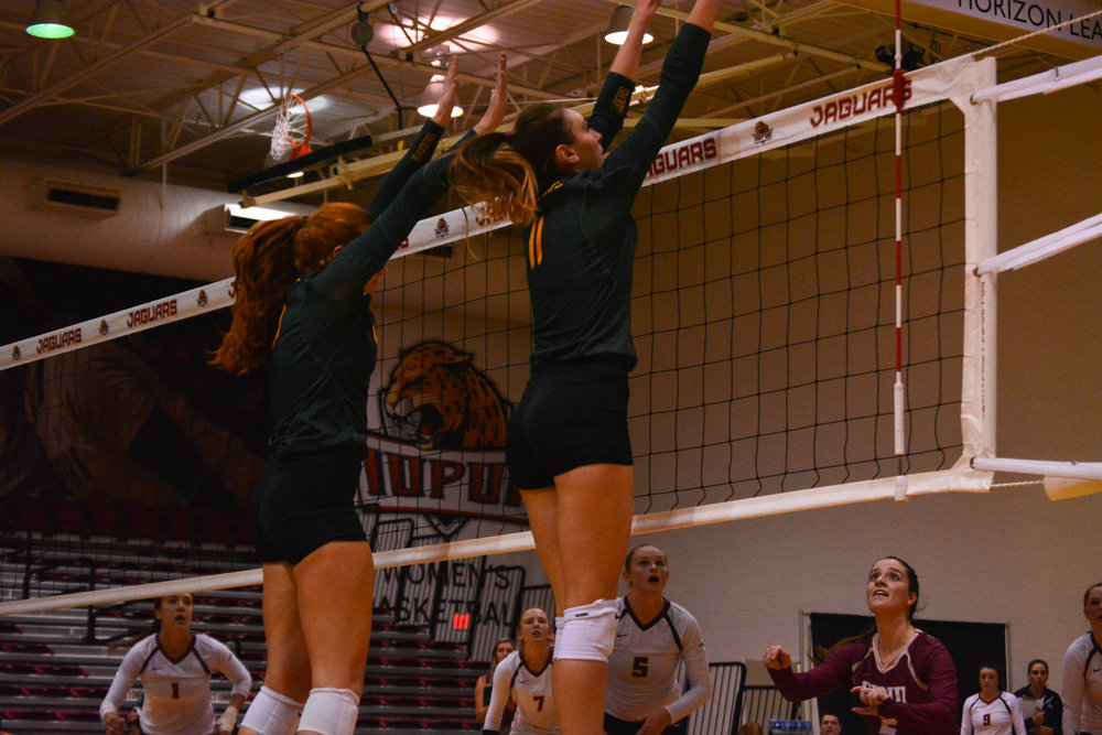 Celia Powers and her teammate for Wright State go up for a block.