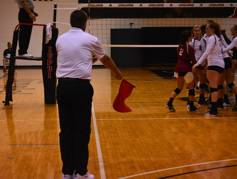The line judge signals a Wright State score. IUPUI gathers after the point.