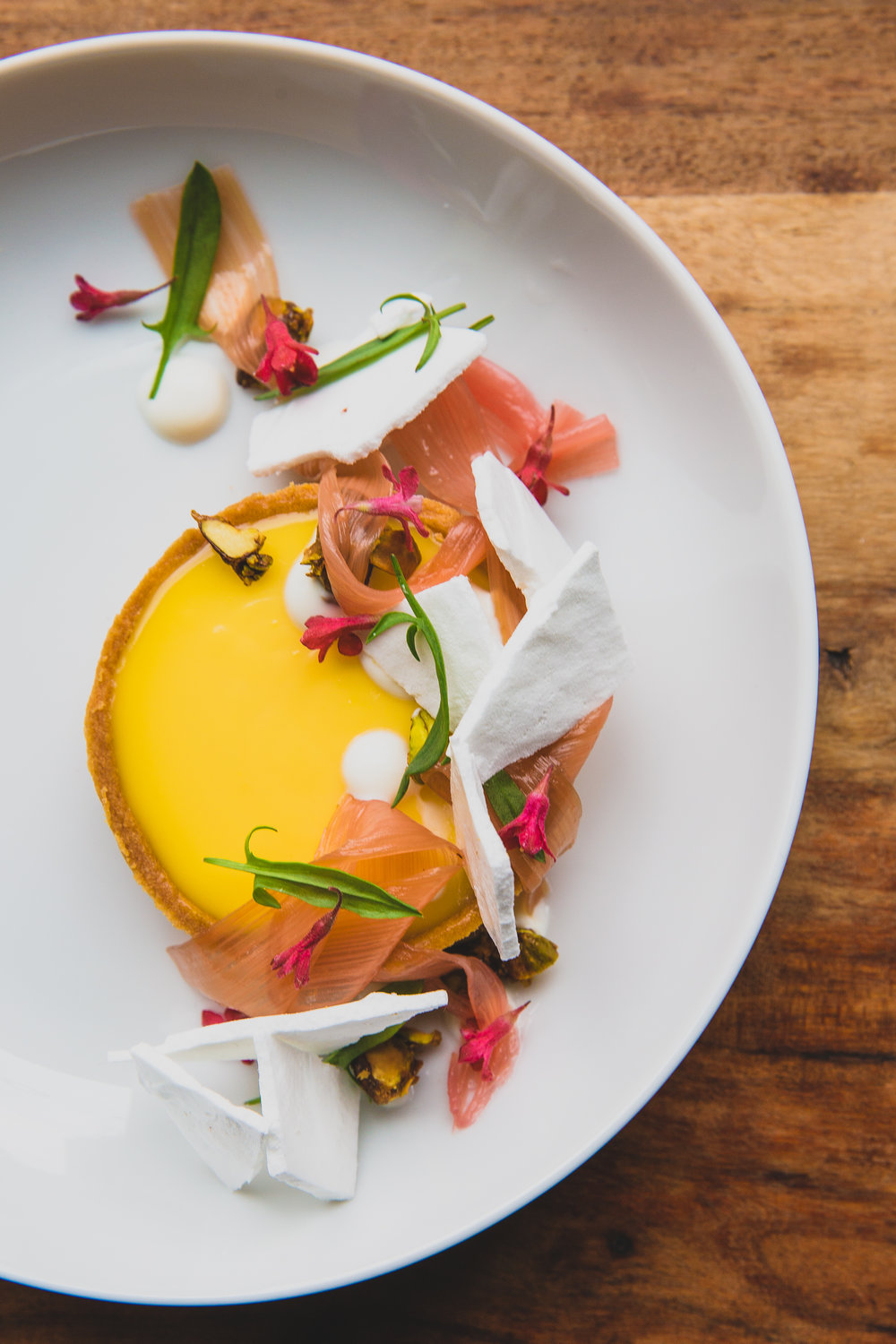 Pistachio lemon tart with rhubarb, honey creme fraiche, meringue shards // Photo credit: When They Find Us