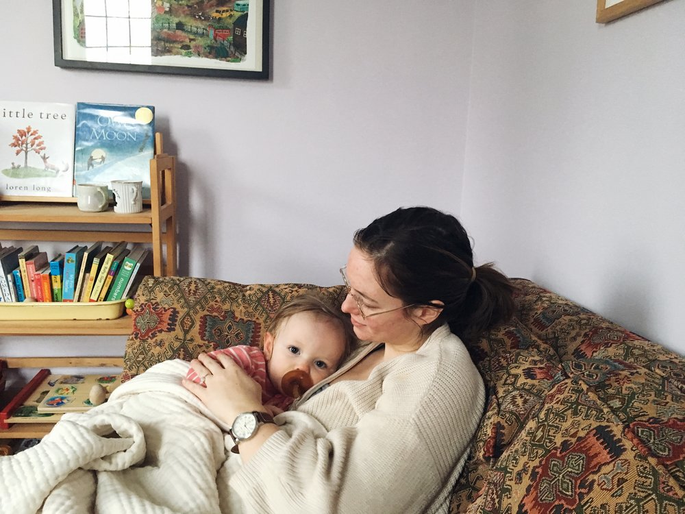 mother and child resting on a couch by samantha spigos