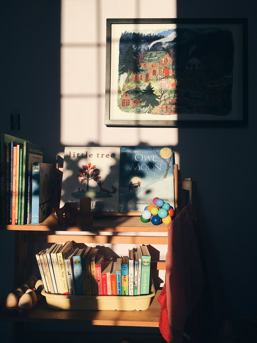 purple walled room with children bookcase filled with colorful toys and books by samantha spigos