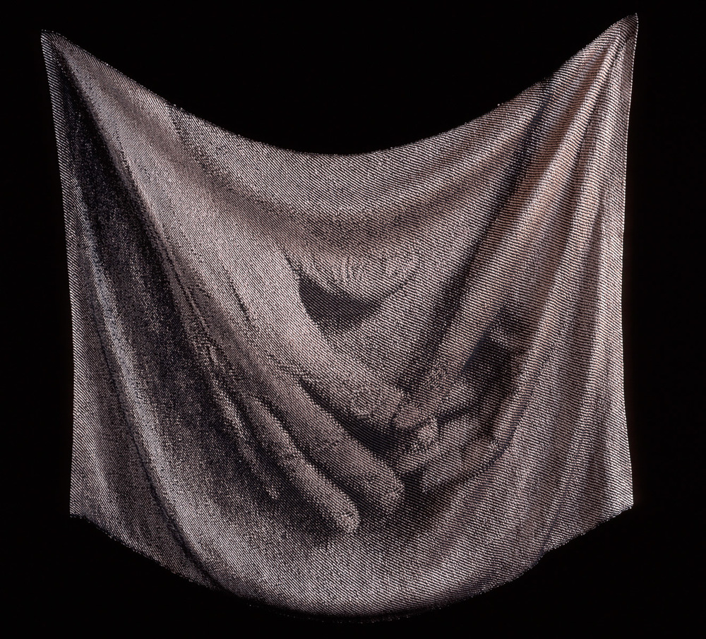 Presenceo Absence Light Touch II  1998 Cotton Rayon Hand woven Work represents the touch of the hand on cloth. Image is frame from a video taken as a person manipulates cloth. The image is woven into the cloth and the cloth is draped to resemble the image of the draped cloth.