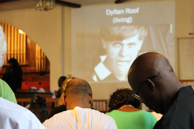 The Record photo/ Jenna Carpenter   A picture of Dylann Roof, suspect in the Charleston shooting that left nine people dead, is displayed during a Friday night vigil for the victims at St. Paul AME Church in St. Augustine. Rev. Rawls told those in attendance to forgive him.