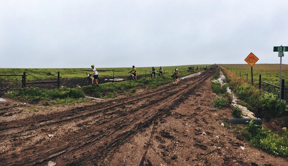 Riders carry their bikes through the mud. Some attempt to ride through, but are only bogged down and spend more time cleaning their bikes than the others.