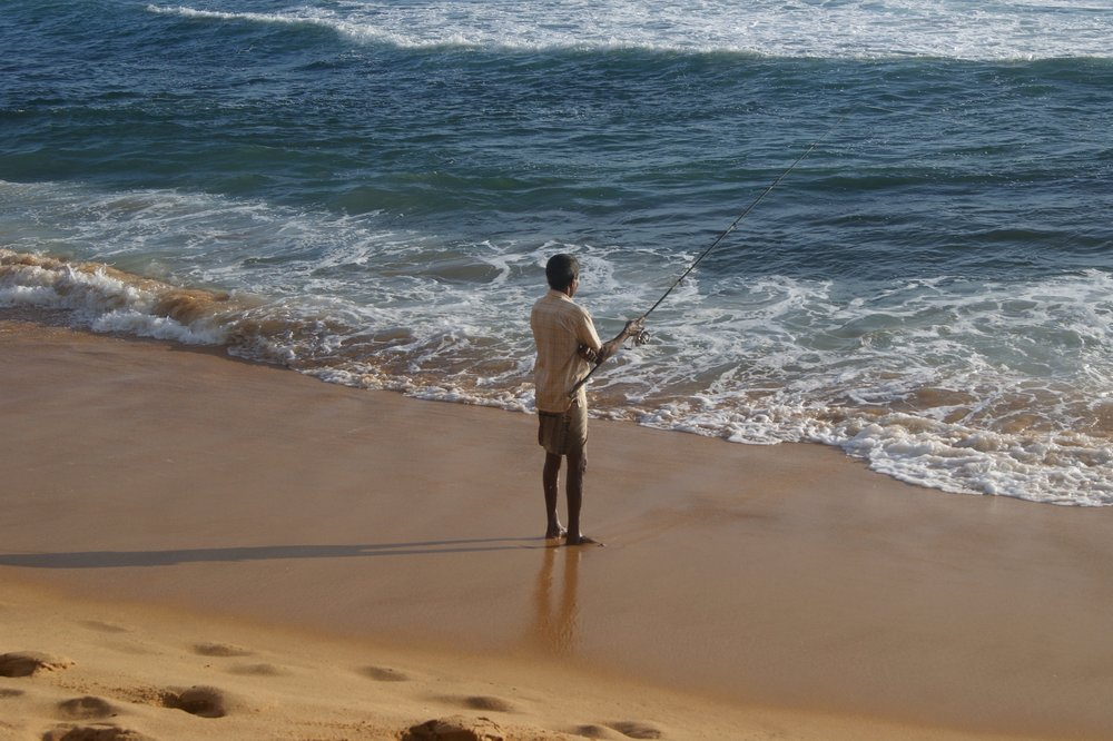 A man from Hikkaauwa, India, fishing on the beach.