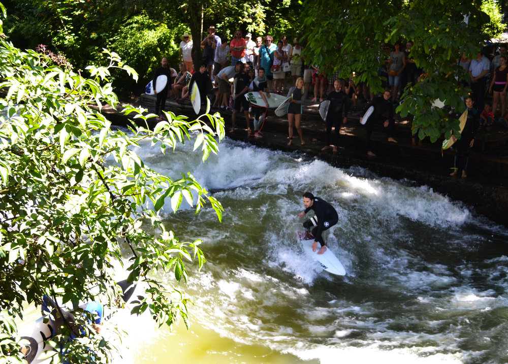 A surfer catching a wave during summer time at the Eisbach Wave, Germany.