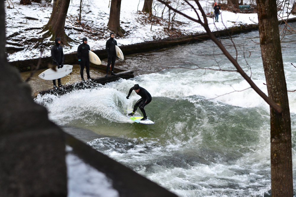 A surfer catching a wave in the middle of winter at the Eisbach Wave, Munich, Germany.