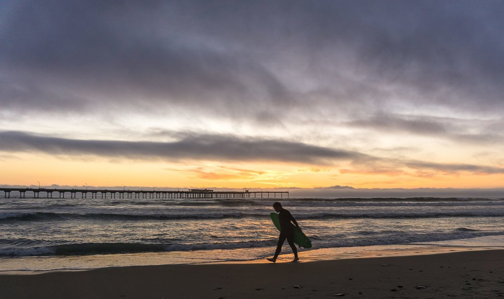 A surfer at sunset coming back from a surf session in San Diego. One more reason to move to San Diego, no?