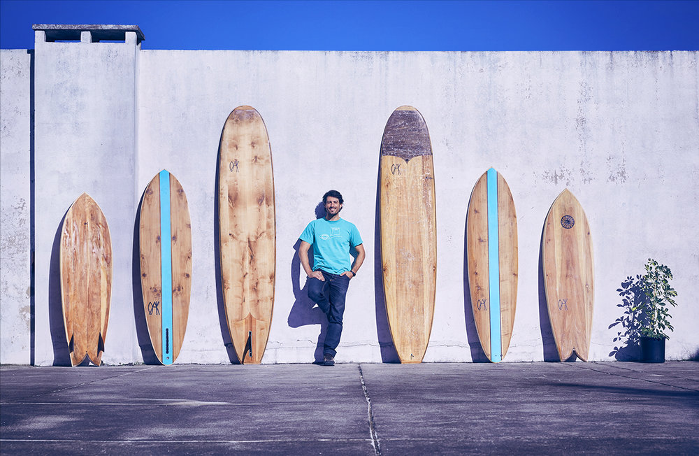 The founder of Oak Surfboards, João, with six surfboards he handshaped.