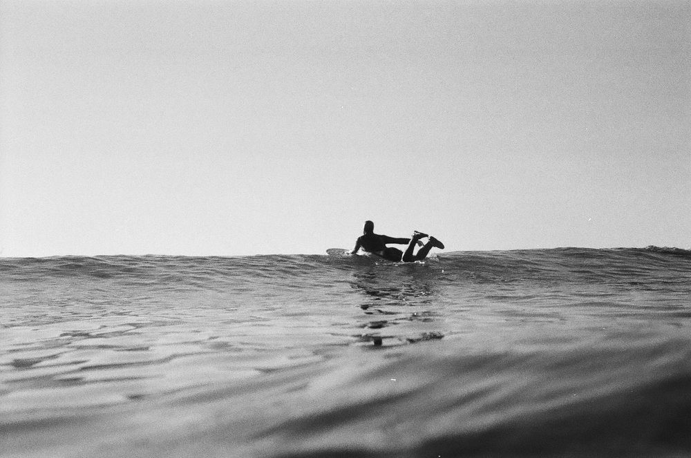 A surfer paddling out towards the depth of the sea. Photographer Maks Eidelson