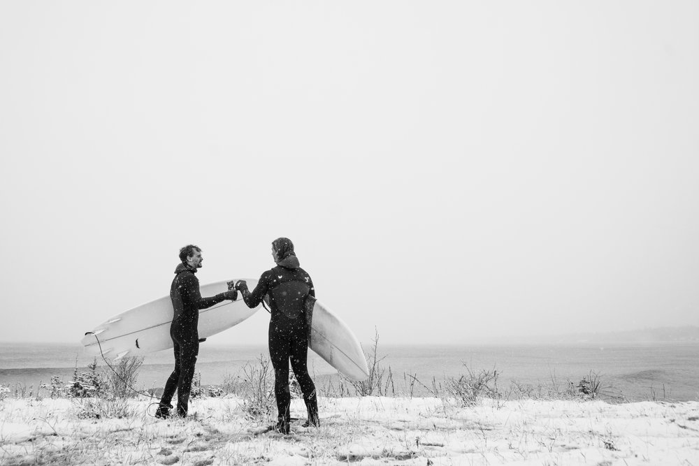 Two friends enjoying a cold brew after a surf session in the middle of winter. Minnesota, USA by Taylor Somerville
