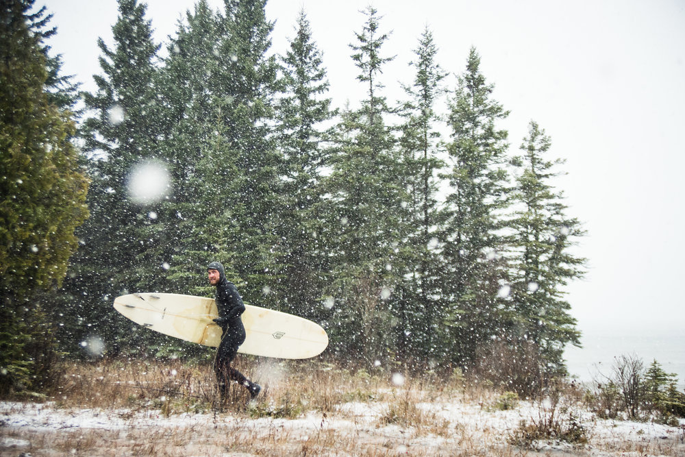 Walking in the cold towards the car after a long day of surfing in Minnesota. Photo Taylor Somerville