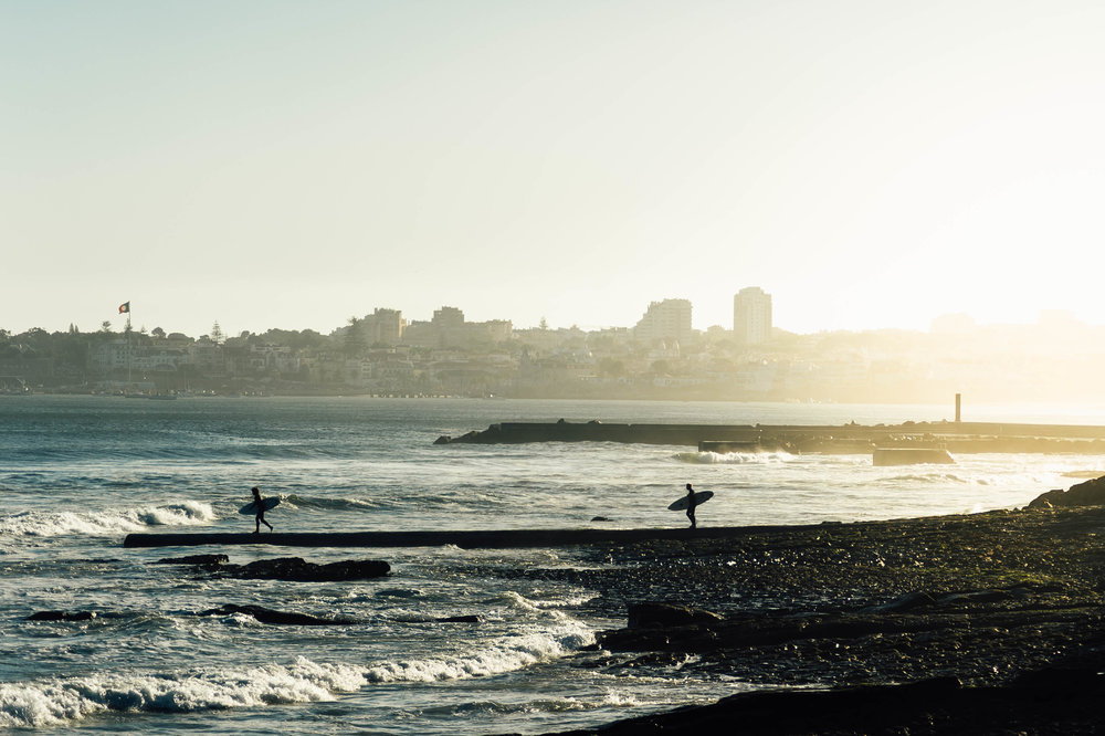 Two surfers running into the sea. Photo by Hugo Filipe Silva