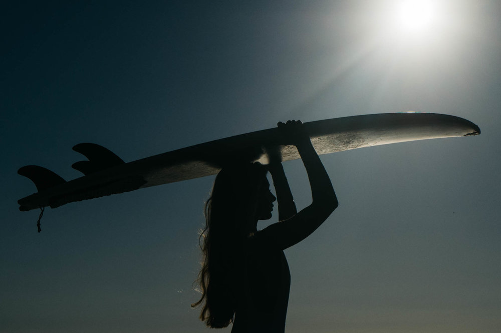 A Surfer in Portugal with the sunshine behind her. Photo by Hugo Filipe Silva