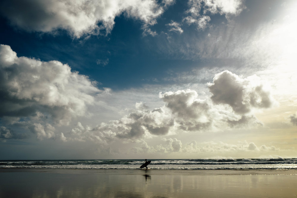 An empty beach and a surfer running towards the waves. Photo by Hugo Filipe Silva