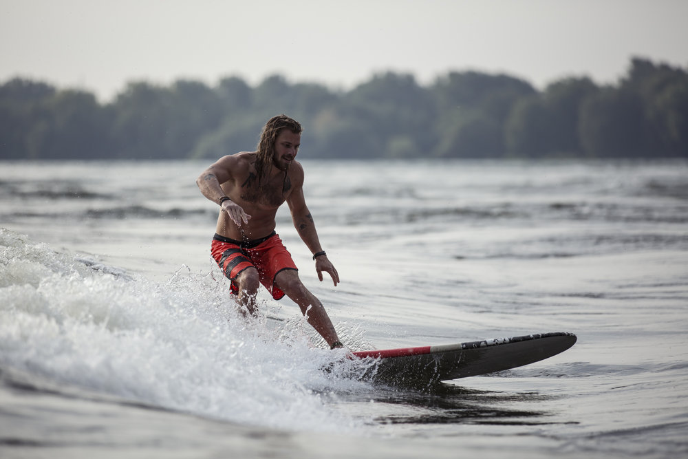 Voyage Grand V's ambassador, Jérémie Gauthier-Lacasse, surfing on the Saint-Lawrence River in Montreal. Photo taken by Alexandra Côté-Durrer