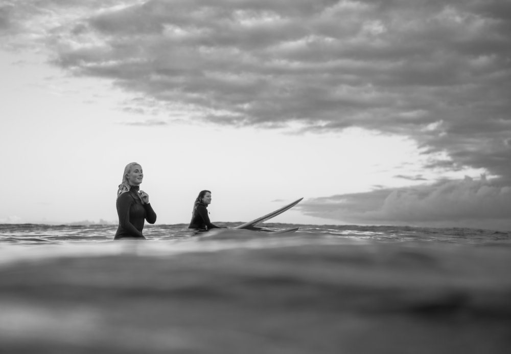 Two female surfers in the frigid water of the Canadian West Coast. Tofino, British Columbia. Photo by Bryanna Bradley