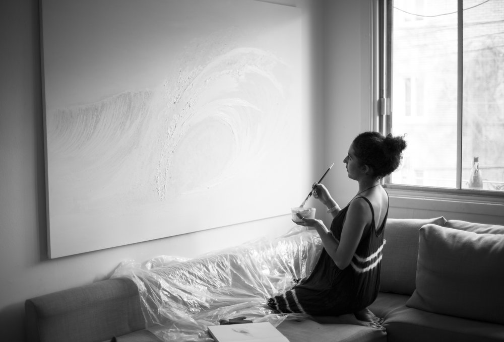 Nathalie Minerva painting white waves. Photo by Alexandra Côté-Durrer