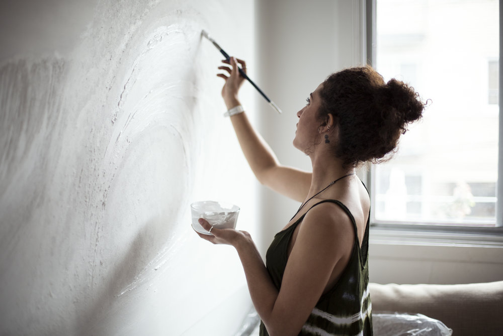 Canadian Artist Nathalie Minerva painting waves in her living room. Photo by Alexandra Côté-Durrer