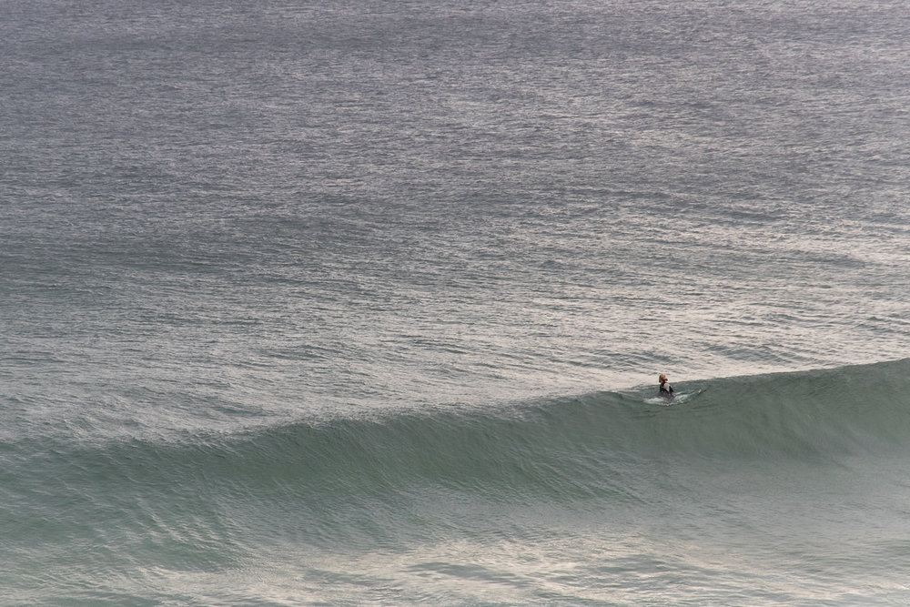 A surfer paddling into an empty lineup. Captured by Susan Czyzo