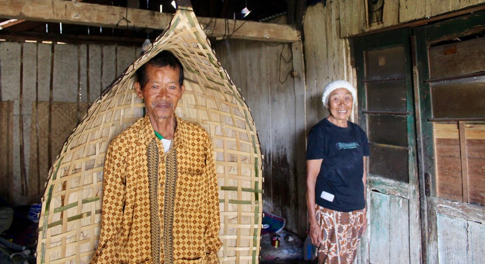 Pak Mahrumi modeling his  kowangan  with his wife in their home near Wonosobo