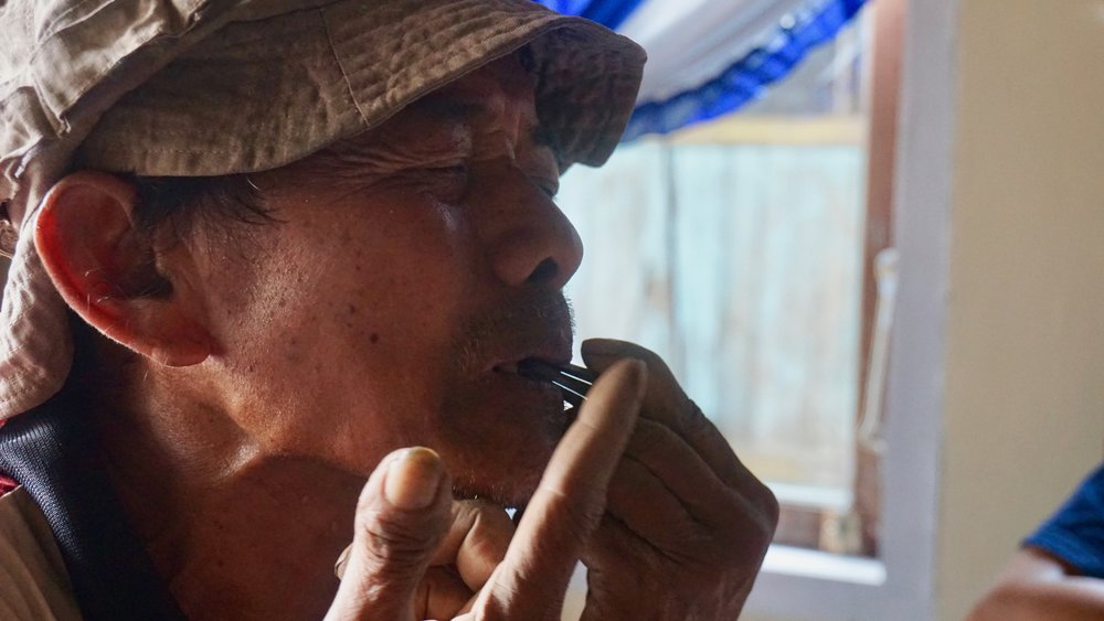 Predi's neighbor, Pak Cican, tries out my os komuz jaw harp.