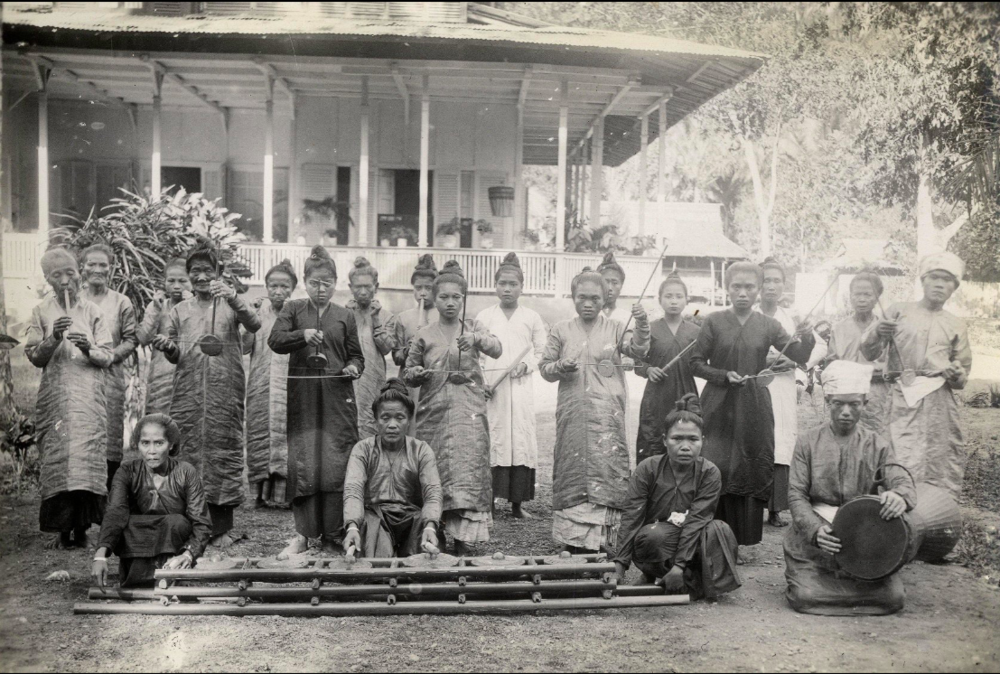 Sangirese priestesses of the Tabukan Kingdom pose with oli instrumentation - oli mouth harp, arbabu fiddle, sasaheng bamboo buzzers, and bangs flute. In the foreground is a set of kulintang gongs, and to the right is a tagonggong. in Tabukan, Sangihe Besar, 1927. Courtesy Leiden University Libraries Digital Collections.