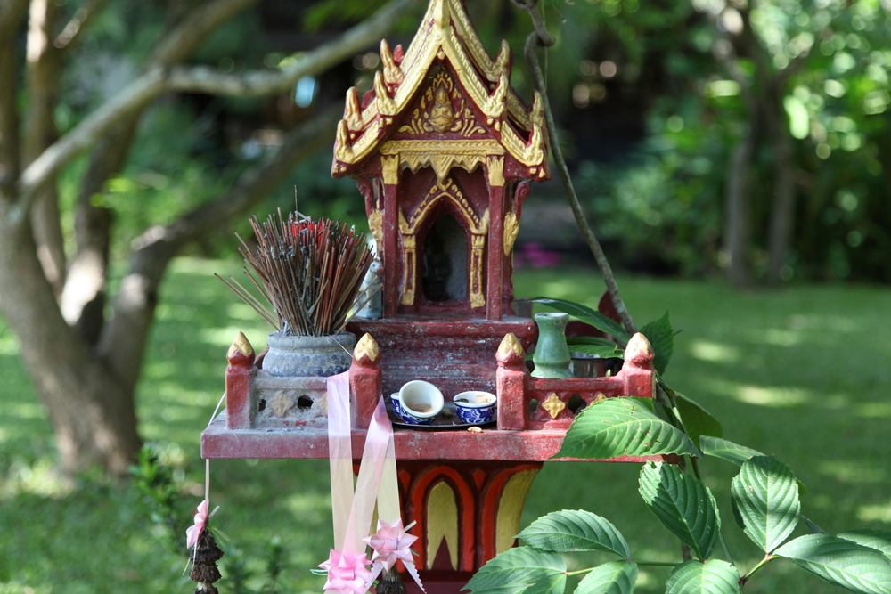 "Spirit house at Baan Hom. The spirit house is a house for the spirits to live in. In Christopher's words ""Thais are afraid of having the wrong relationship with the spirits. The spirits are everywhere and providing a house for the spirits who already live on the land where you live is a priority, more important even than building your own house.You must be able to say to the spirits, ""Look, here's an even more beautiful house for you. Here's a beautiful palace complete with these gifts, and in exchange please allow us to share this space with you for the time being."" What a beautiful and considerate  concept. I love Thailand for that. I loved seeing them all over Thailand. They are so beautiful. They are outside of houses , businesses, shrines and  temples. They are maintained just as an alter would be maintained. Water ,food, incense (and sometimes a Red Bull) are offered everyday to the spirit houses."