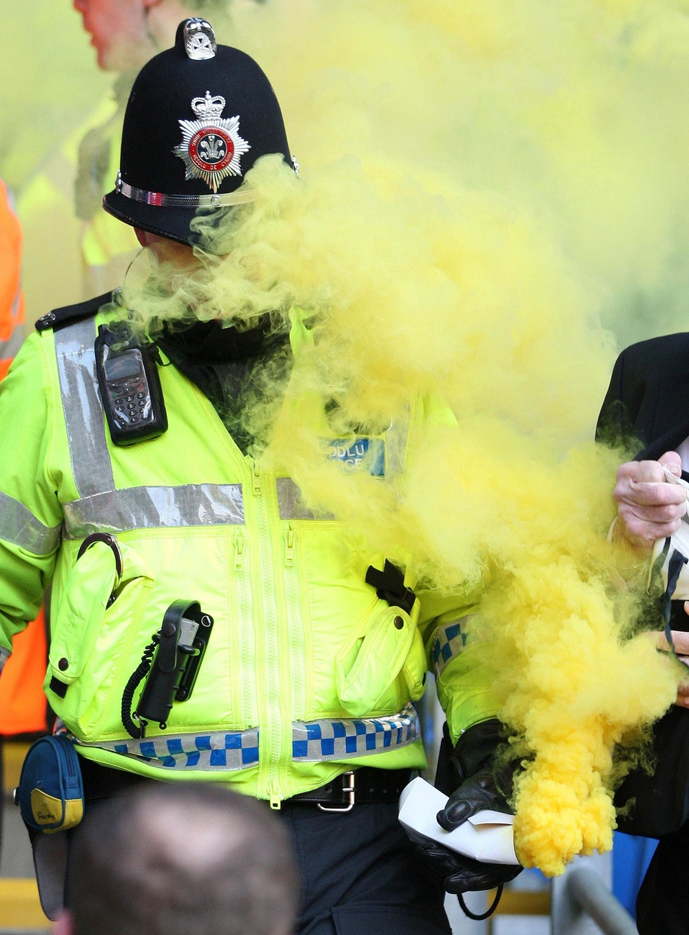 Police officer removes a smoke bomb from football match