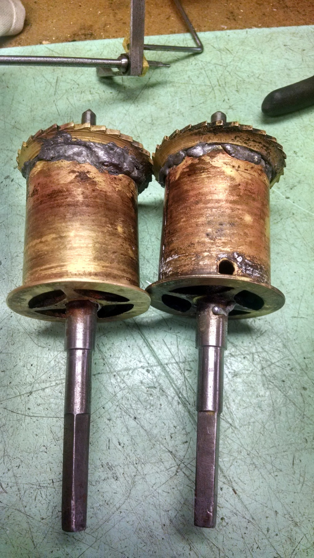These are the winding barrels where the cable is held when the clock is wound. They were poorly repaired by a previous repair person. You can see all the extra solder.